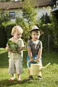 Germany, Bavaria, Boys with savoy and watering can - stock photo