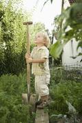 Germany, Bavaria, Boy holding shovel in garden Stock Photos