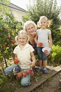 Germany, Bavaria, Grandmother with children in vegetable garden - stock photo