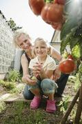 Germany, Bavaria, Grandmother and granddaughter working in vegetable garden - stock photo