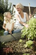 Germany, Bavaria, Grandmother with children working in vegetable garden - stock photo