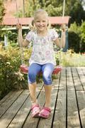Stock Photo of Germany, Bavaria, Girl swinging on swing, smiling, portrait