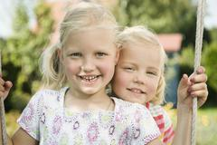 Germany, Bavaria, Girls swinging on swing, smiling, portrait - stock photo