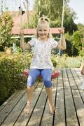 Germany, Bavaria, Girl swinging on swing, smiling, portrait - stock photo