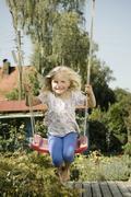 Stock Photo of Germany, Bavaria, Girl swinging on swing