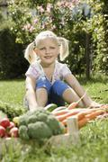 Germany, Bavaria, Girl sitting in vegetable gaeden, smiling, portrait Stock Photos