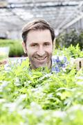 Germany, Bavaria, Munich, Mature man in greenhouse with rocket plants - stock photo