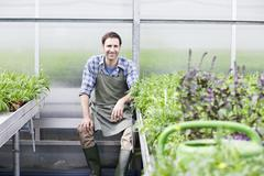 Germany, Bavaria, Munich, Mature man in greenhouse between rocket plant - stock photo