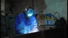 Stock Video Footage of Male wearing uniform welds with welding machine torch, click for HD