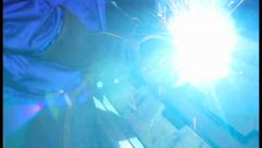 Welding process as man in helmet lights up weld torch, click for HD - stock footage
