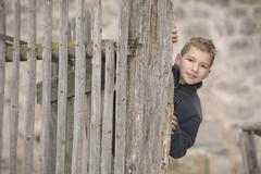 Stock Photo of Germany, Bavaria, Boy standing behind fence, portrait