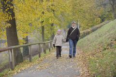 Germany, Bavaria, Mother and daughter walking on footpath in autumn Stock Photos