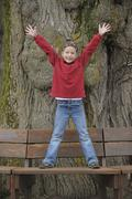 Stock Photo of Germany, Bavaria, Girl standing on bench with arms up, portrait