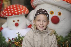 Stock Photo of Germany, Bavaria, Girl in front of decoration mushroom, smiling, portrait
