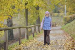 Germany, Bavaria, Girl walking on footpath, smiling, portrait Stock Photos