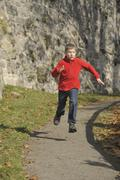 Germany, Bavaria, Boy running on footpath Stock Photos