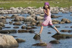 Sweden, Molle, Girl balancing on rock in water Stock Photos