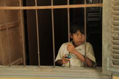 Cambodian Children young boy looking out  window - stock photo