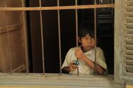 Stock Photo of Cambodian Children young boy looking out  window