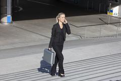Stock Photo of Germany, Bavaria, Munich, Businesswoman on stairs with briefcase and talking on