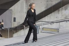 Germany, Bavaria, Munich, Businesswoman walking on stairs with briefcase, - stock photo