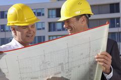 Germany, Bavaria, Munich, Engineers with blue print, smiling - stock photo