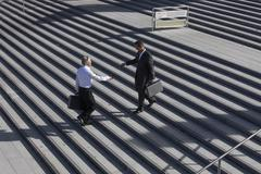Germany, Bavaria, Munich, Engineers shaking hands on stairs Stock Photos
