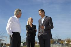 Germany, Bavaria, Munich, Business people standing against sky, smiling - stock photo