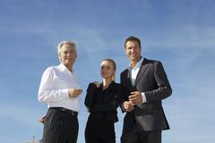 Stock Photo of Germany, Bavaria, Munich, Business people standing against sky, smiling,