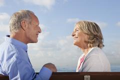 Spain, Mallorca, Senior couple sitting on bench at sea shore, smiling - stock photo