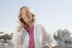 Spain, Mallorca, Palma, Senior woman on phone, smiling Stock Photos