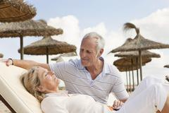 Spain, Mallorca, Senior man looking at woman resting on deck chair at beach - stock photo