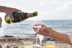 Spain, Mallorca, Senior couple drinking sparkling wine at beach - stock photo