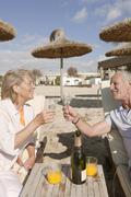 Stock Photo of Spain, Mallorca, Senior couple drinking sparkling wine at beach