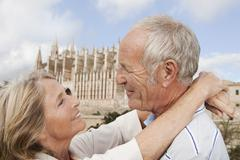 Spain, Mallorca, Palma, Senior couple smiling with Cathedral Santa Maria, - stock photo