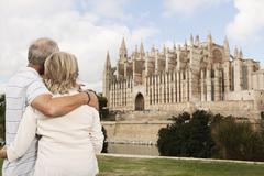 Spain, Mallorca, Palma, Senior couple smiling with Cathedral Santa Maria - stock photo