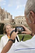 Spain, Mallorca, Palma, Senior couple smiling taking picture with Cathedral - stock photo