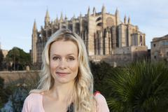 Spain, Mallorca, Palma, Young woman standing with St Maria Cathedral in - stock photo