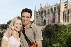 Spain, Mallorca, Palma, Couple standing with St Maria Cathedral in background, - stock photo