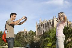 Spain, Mallorca, Palma, Couple photographing with mobile phone at St Maria - stock photo