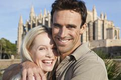Spain, Mallorca, Palma, Couple hugging with St Maria Cathedral in background, - stock photo