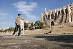 Spain, Mallorca, Palma, Couple walking with St Maria Cathedral in background - stock photo