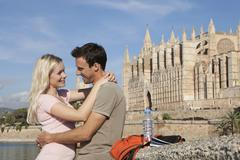 Spain, Mallorca, Palma, Couple embracing with St Maria Cathedral in background, - stock photo