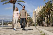 Stock Photo of Spain, Mallorca, Palma, Couple walking along allee, smiling