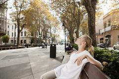 Stock Photo of Spain, Mallorca, Palma, Young woman resting on bench