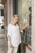 Spain, Mallorca, Palma, Young woman at shop window, smiling, portrait Stock Photos