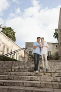 Spain, Mallorca, Palma, Couple with guidebook, smiling - stock photo
