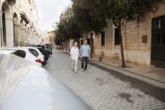 Spain, Mallorca, Palma, Couple walking along street - stock photo
