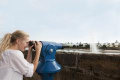 Spain, Mallorca, Palma, Young woman looking through telescope, smiling Stock Photos