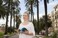 Spain, Mallorca, Palma,Young woman with guidebook, smiling - stock photo